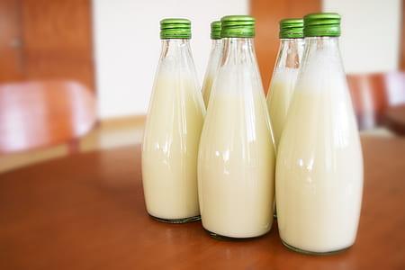 five bottles of milks on table
