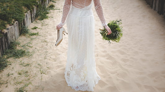 woman in wedding gown walking on sand