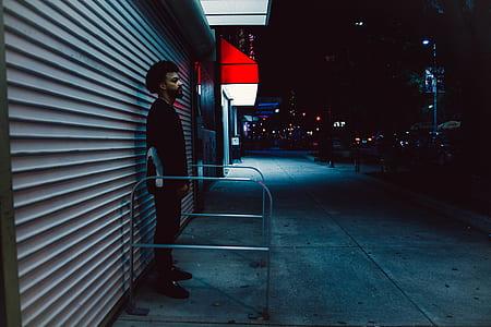 man in black shirt standing behind gray roller shutter