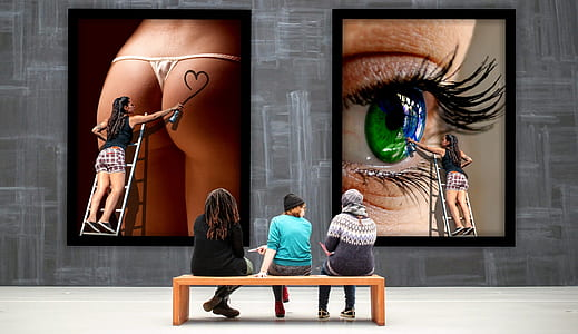 three people sitting on wooden bench in front of two artworks