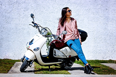 woman in pink long-sleeved shirt and blue jeans holding white motor scooter
