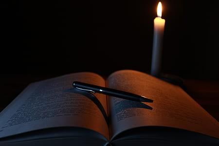 black click pen on open book near cnadle