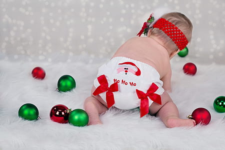 baby in white diaper playing green and maroon baubles
