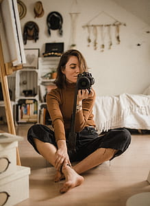 focus photo of woman in brown sweater and black bottoms holding black DSLR camera