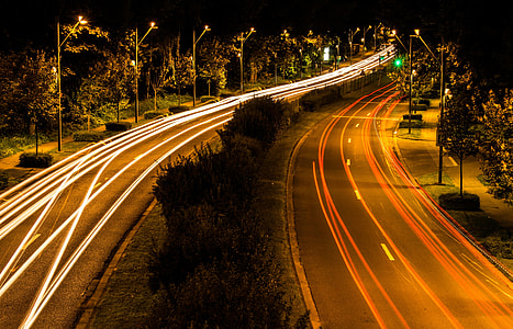 timelapse photography of passing cars in two highways with center isle during nighttime