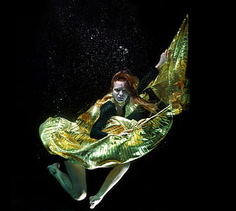 woman in yellow and black dress underwater