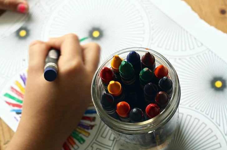 person holding blue color crayon