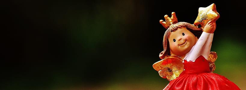 red dressed girl ceramic figurine macro photography