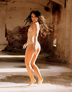 woman wearing beige body suit about to jump photo