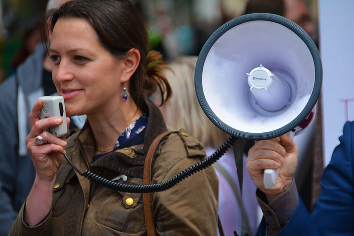 Royalty-Free photo: Woman in brown jacket holding megaphone during ...