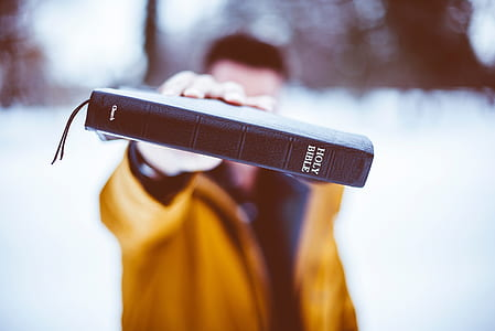 selective focus photography of man wearing brown jacket holding brown Holy Bible