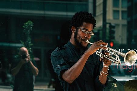 man wearing black dress shirt playing silver trumpet