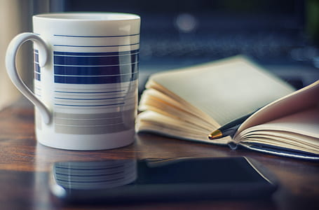 white and blue ceramic mug beside book