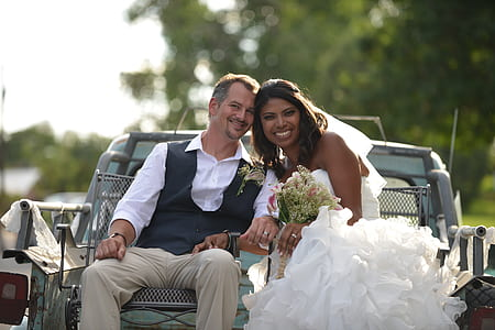 bride and groom riding the back of a truck during daytime