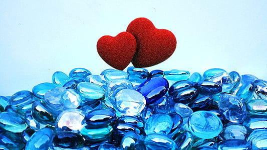blue pebbles with two red hearts on top