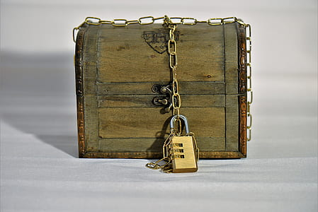 brown wooden trunk box with brass-colored padlock and chain