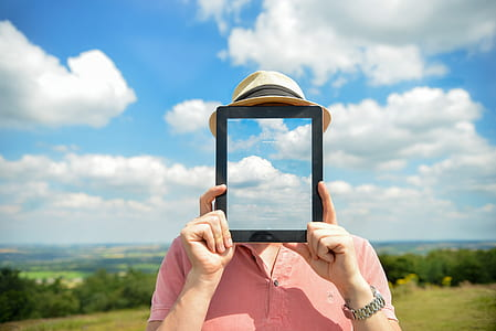 man wearing pink polo shirt holding black iPad with clouds display