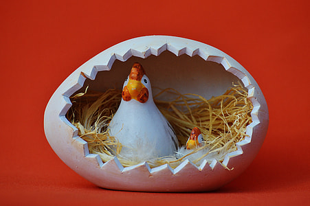 two white-and-red hens inside egg nest figurine