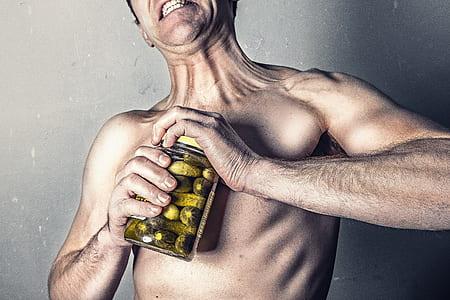 shirtless man opening jar of pickles