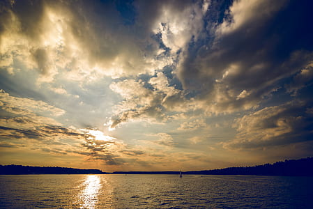 photo of large body of water with sunset background