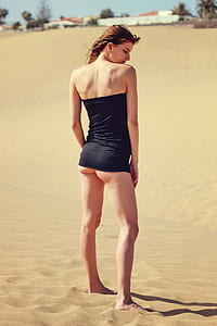 woman black strapless shirt standing on sand at daytime