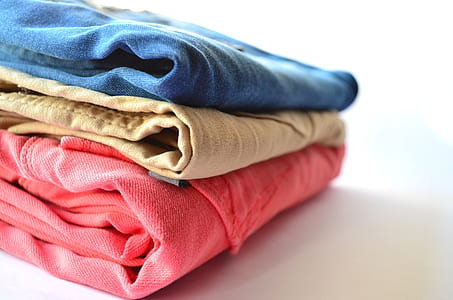 three red, brown, and blue denim bottomes