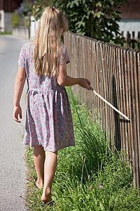 girl holding stick walking beside fence