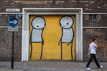 A man walks past a one-way sign and street art background in Shoreditch, East London
