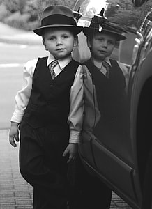 grayscale photography of boy in dress shirt with vest and fedora hat leaning on car