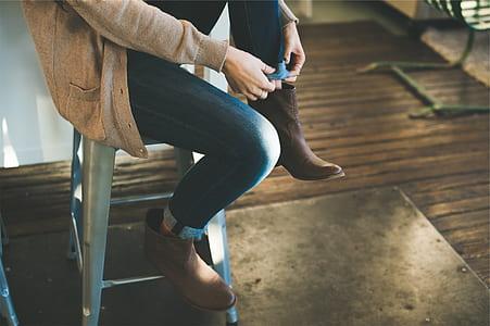 person folding edge of denim pants while sitting on grey stool