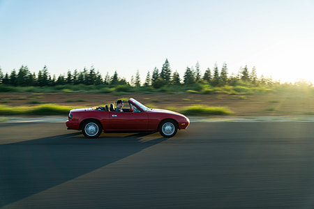 person driving red convertible coupe running on concrete road