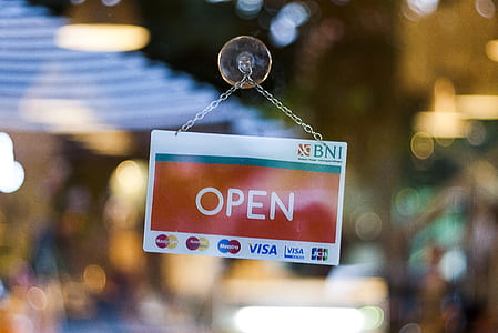 selective focus photographed of open hanging signboard