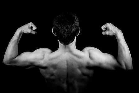 man flexes biceps on dark room
