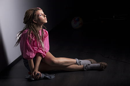 woman in pink shirt sitting on floor