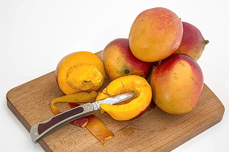 sliced mango beside four mangoes on chopping board