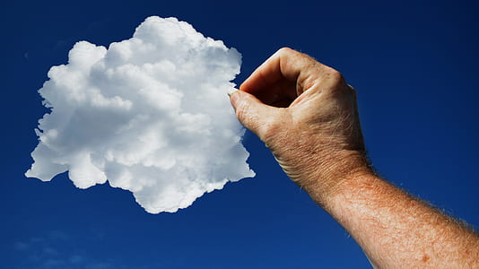 low angle photo of pointing right human arm towards white cloud on blue sky during daytime