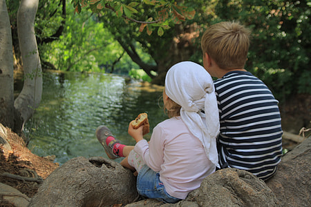 photography of boy and girl sitting on rock
