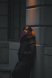 woman leaning on wall during nighttime