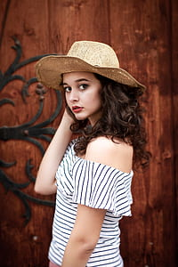 brown haired woman in off shoulder dress wearing brown ahrt