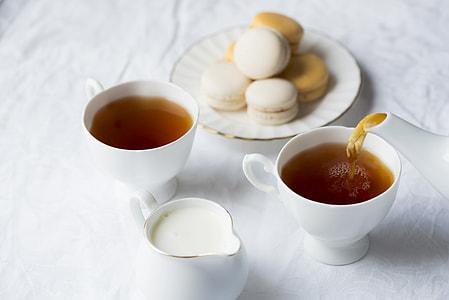 two white ceramic tea cups and white teapot