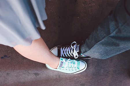 man and woman wearing black and teal low-top sneakers