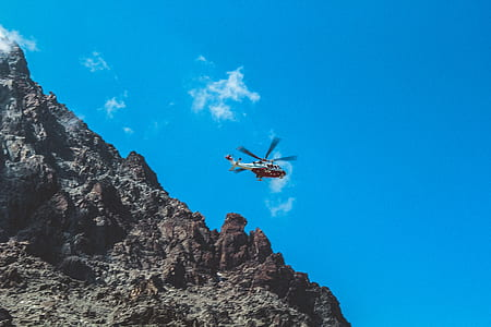 Photography of White and Red Helicopter Flying