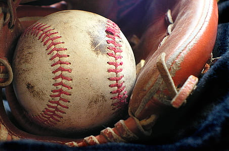 white and red baseball with brown leather baseball glove