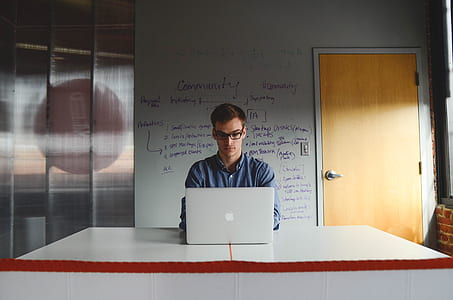 man wearing dress shirt and using MacBook on the table