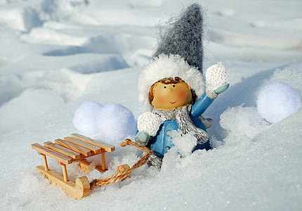 gray and blue dressed doll with sled on snow