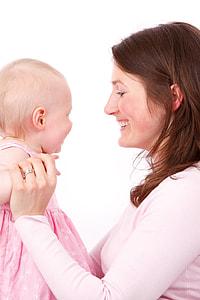mother facing her baby wearing pink sleeveless dress