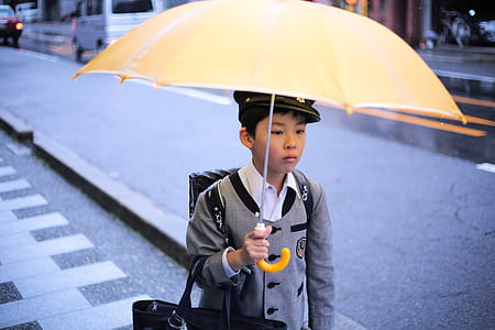 boy wearing school uniform holding a yellow umbrella