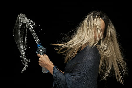 woman holding plastic bottle with water