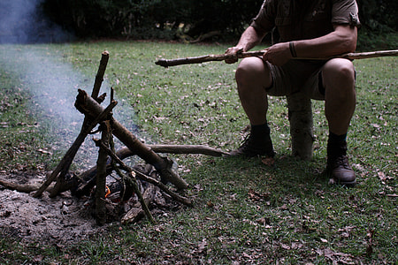 man sitting on log making fire with wood pile during daytime