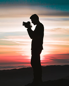 silhouette of a man holding a camera